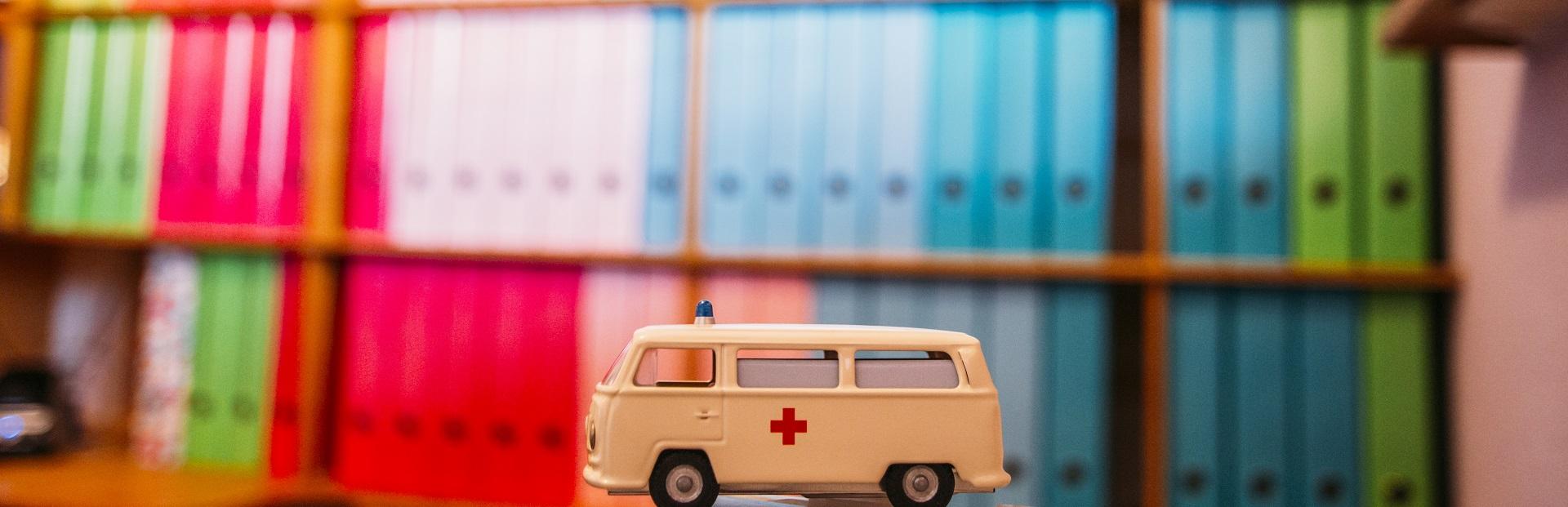 dossiers met speelgoed ambulance ervoor